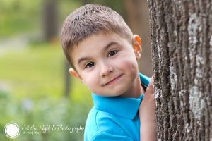 Portrait of a 4 year old boy standing near a tree. Photograph taken at Meadowlark Gardens in Northern Virginia