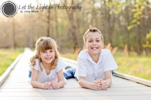 A brother and a sister laying down on an elevated walkway. Portrait taken at the Manassas Battlefield
