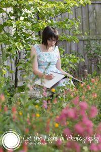 High School Senior Girl sketching in a flower garden. Taken by Fauquier County Senior Portrait Photographer