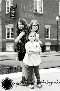 3 Sisters in front of the Candy Factory in Old Town Manassas. Photograph is in black and white.
