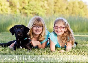 Two sisters and their black lab in the late spring at the Manassas Battlefield