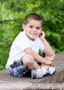5 year old boy sitting on a stone wall at the Manassas Battlefield in Virginia