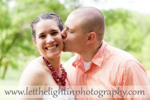Portrait of a couple, husband is kissing the wife on the cheek and she is glowing! Taken at Meadowlark Gardens in Northern Virginia
