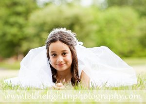 First Communion Portrait of a girl in a white dress with a veil laying inthe grass. Taken in Bristow Virginia