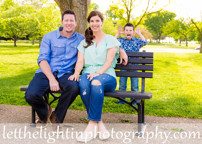 Dc mom and dad sitting on a bench with their child making faces behind them