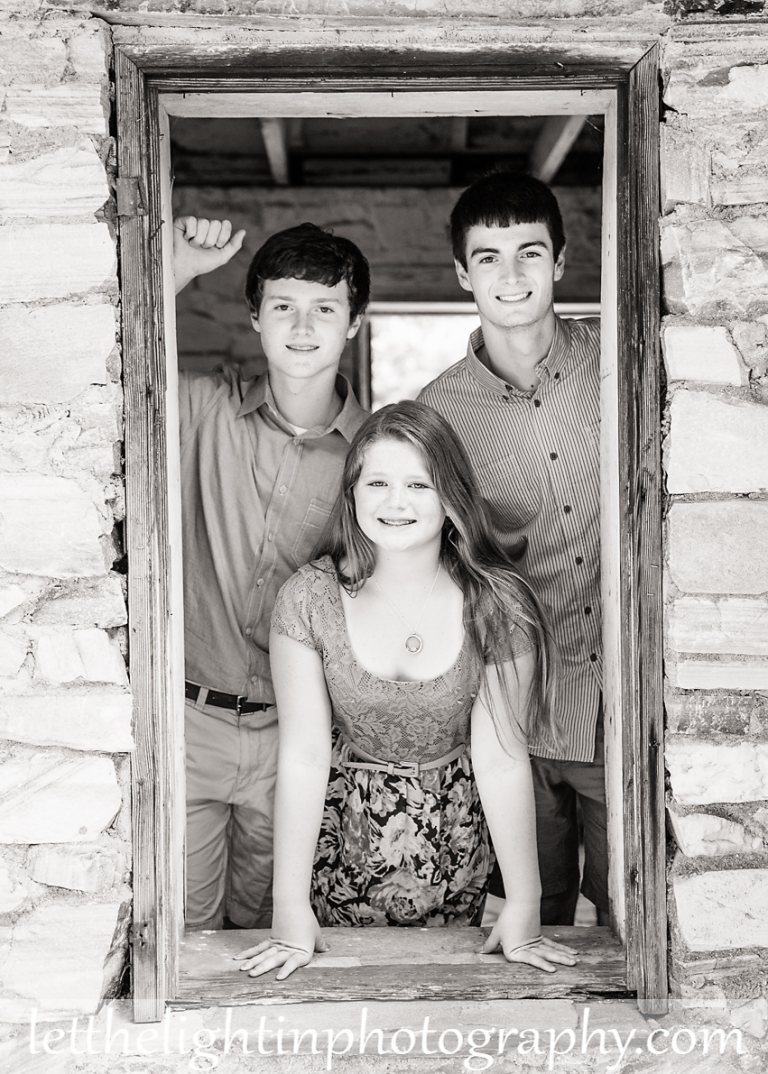 Photo of older siblings looking through a window taken near Haymarket VA