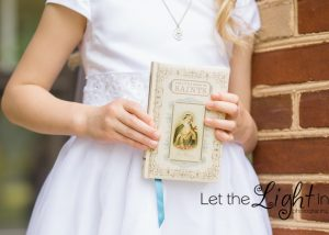 girl holding prayer book with white dress for communion