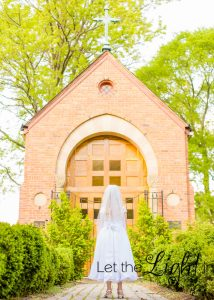 girl standing in front of chapel posing for first communion photos