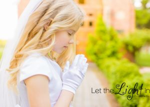 Girl praying with first communion gloves in front of chapel