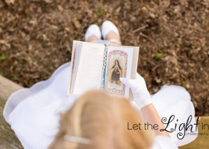 girl looking at prayer book for First Communion Portraits.
