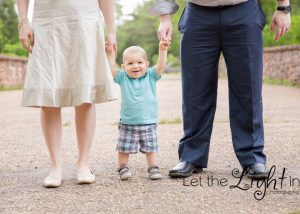 baby standing between parents legs
