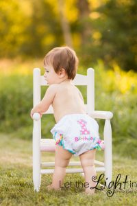 baby with diaper cover toward camera with #1 on it for first birthday