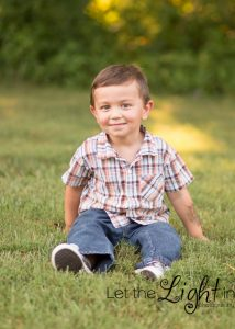3 year old boy sitting in grass near Gainesville VA posing for pictures