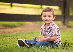 Boy sitting in grass for pictures