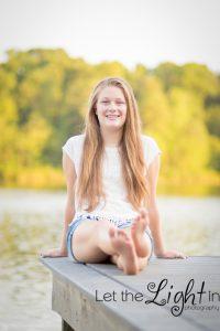 Senior girl posing for portraits on a dock