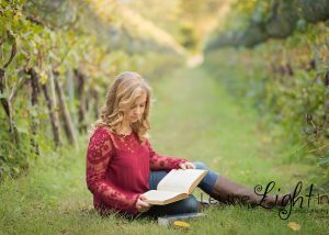 Girl sitting in the grass among the grapevines reading a book.