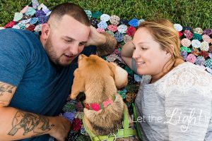 Couple with dog laying on the ground. Portrait Photographer in Prince William County