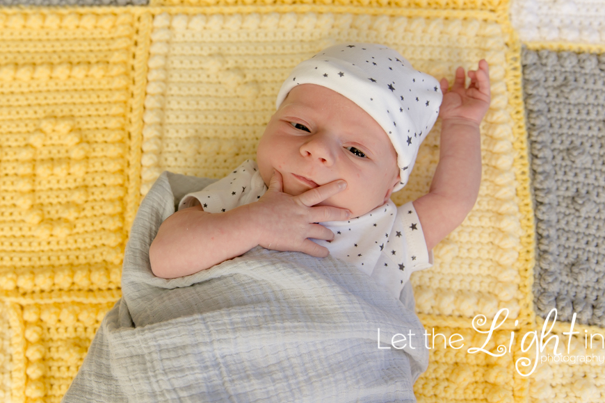 baby looking up at camera holding his face by Local newborn photographer in Bristow Virginia
