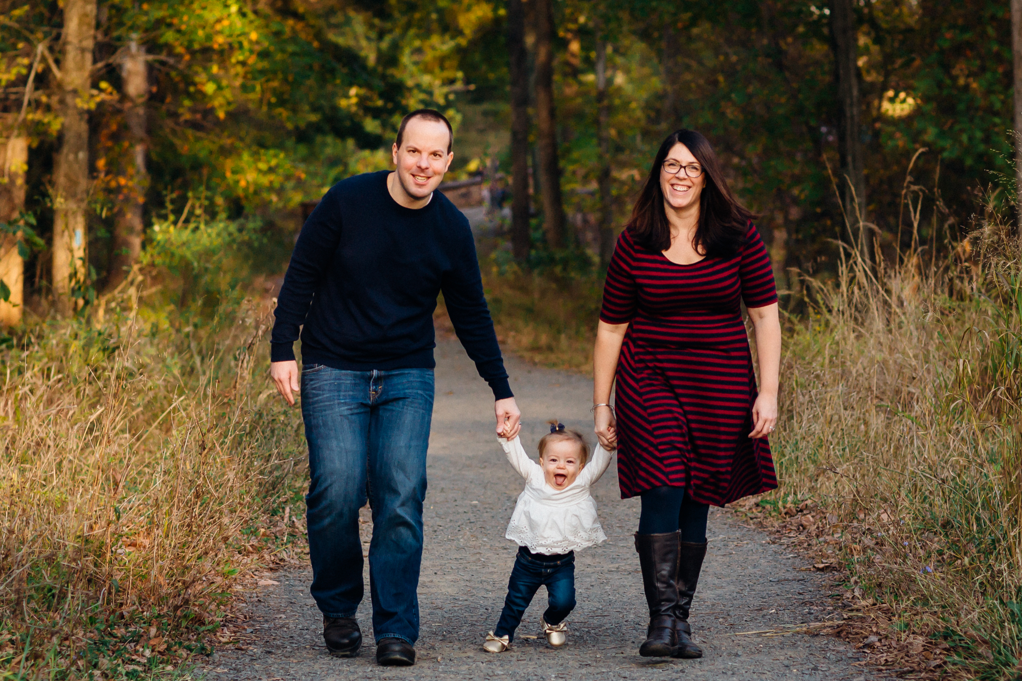 parents walking with 1 year old between them