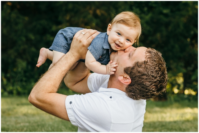 Little boy getting kissed by dad, feet in the air.