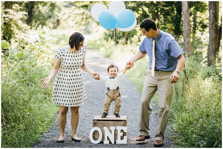 One year old boy and family posing with ONE sign and balloons for his birthday