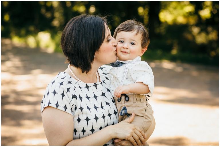 Mom kissing son on the cheek.