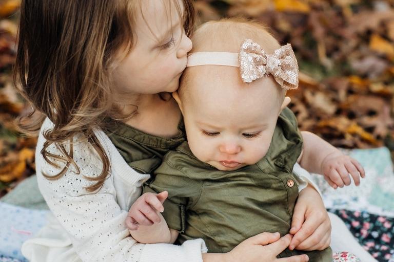 Older sister kissing baby sister