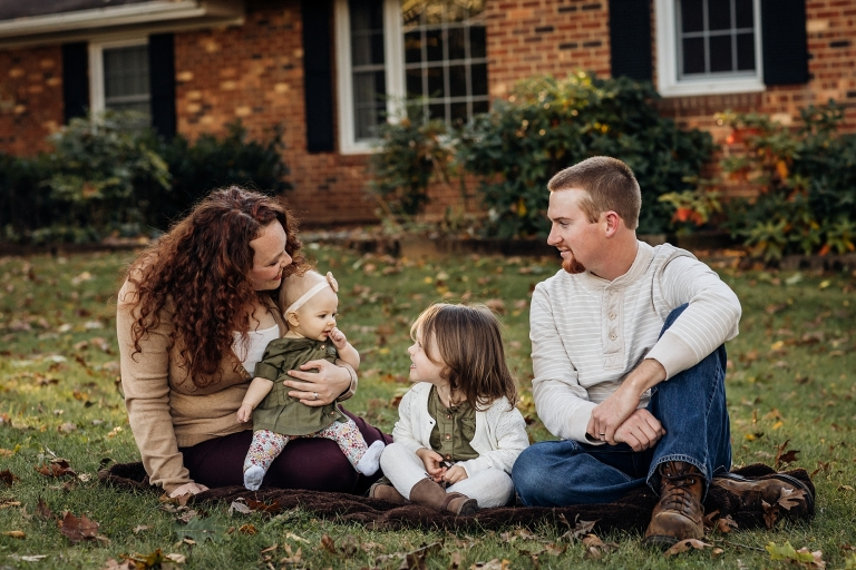 family sitting in grass in front of their home for photos.