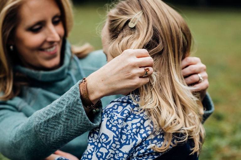 mom with her hands in daughters hair