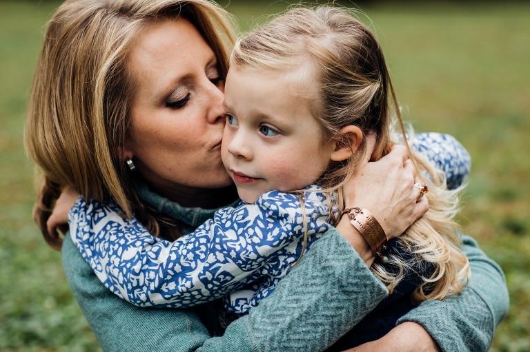 mom kissing daughter