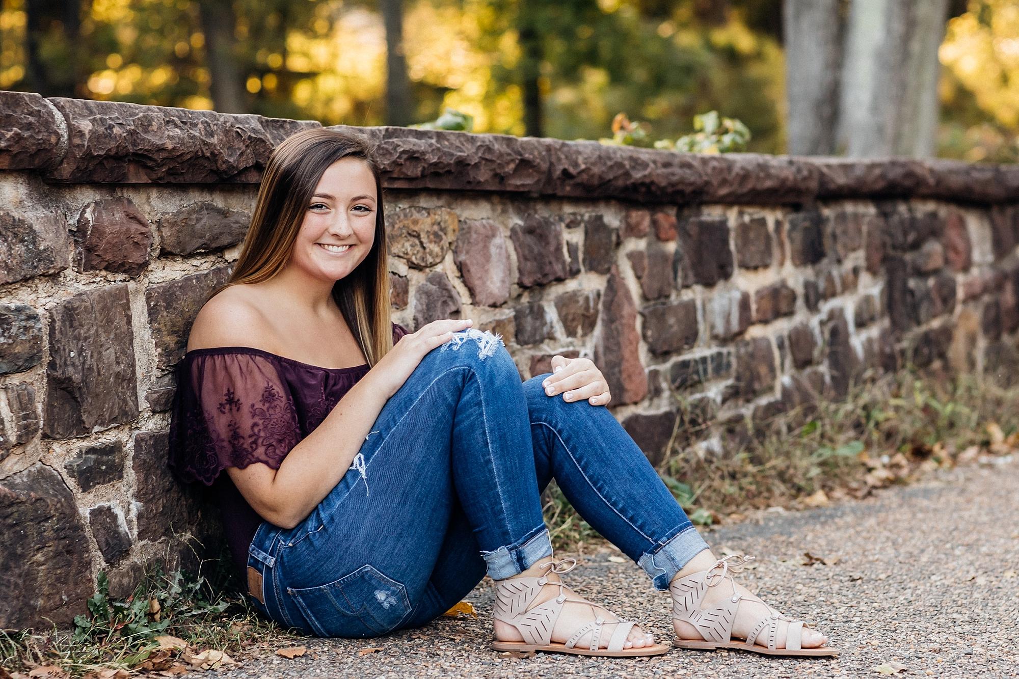 Senior girl from Northern Virginia sitting by Stone Bridge in Manassas