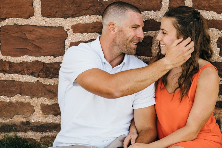 man moving hair out of fiancé's face.