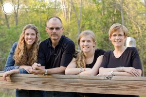 Family of four with teenage girls leaning against a fence rail. Portrait taken in Manassas Virginia