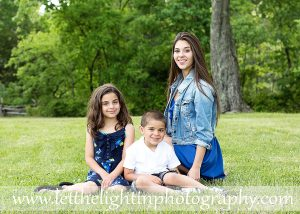 Portrait of three children in the late spring season with a lot of green leaves. Taken by Wendy Atkinson