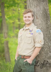 Boy Scout standing next to tree at Camp Snyder