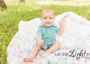 1 year old boy waving at camera