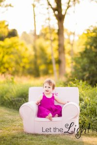 1 year old girl sitting in a chair outside for portraits