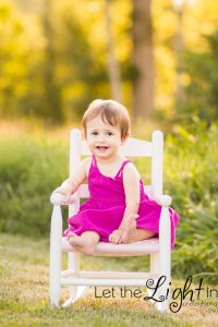 1 year old sitting in a rocking chair, golden light behind her near stone bridge in manassas