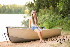 Senior Girl sitting on boat near a lake