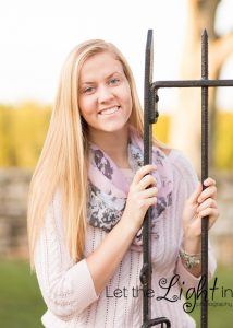 Girl leaning on iron gate to pose for Senior Pictures