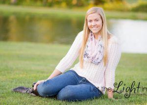 girl sitting in the grass posing for senior pictures in Haymarket VA 20169