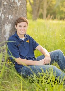 High School Senior sitting against tree with WV University shirt on.