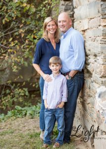 Family of 3 posing for family pictures at Chapman's Mill in Haymarket Virginia